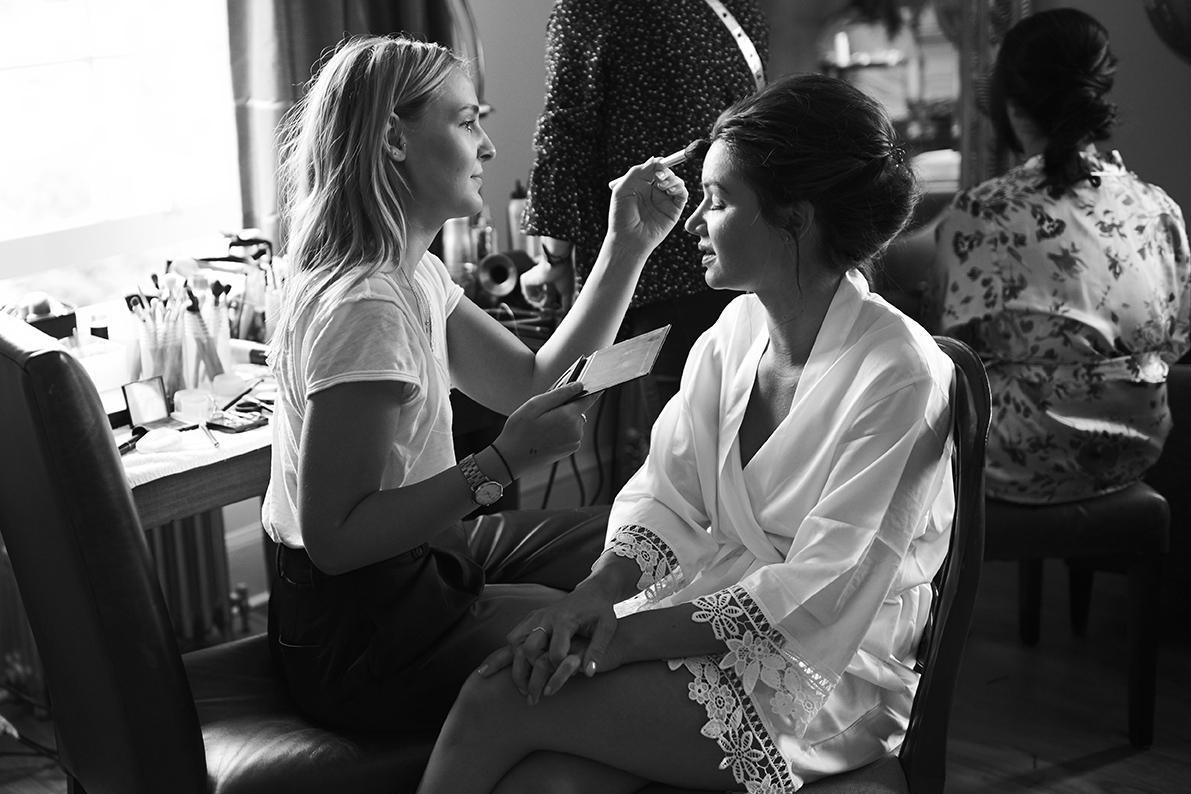 make up artist applies make up on bride's forehead at hotel du vin kent