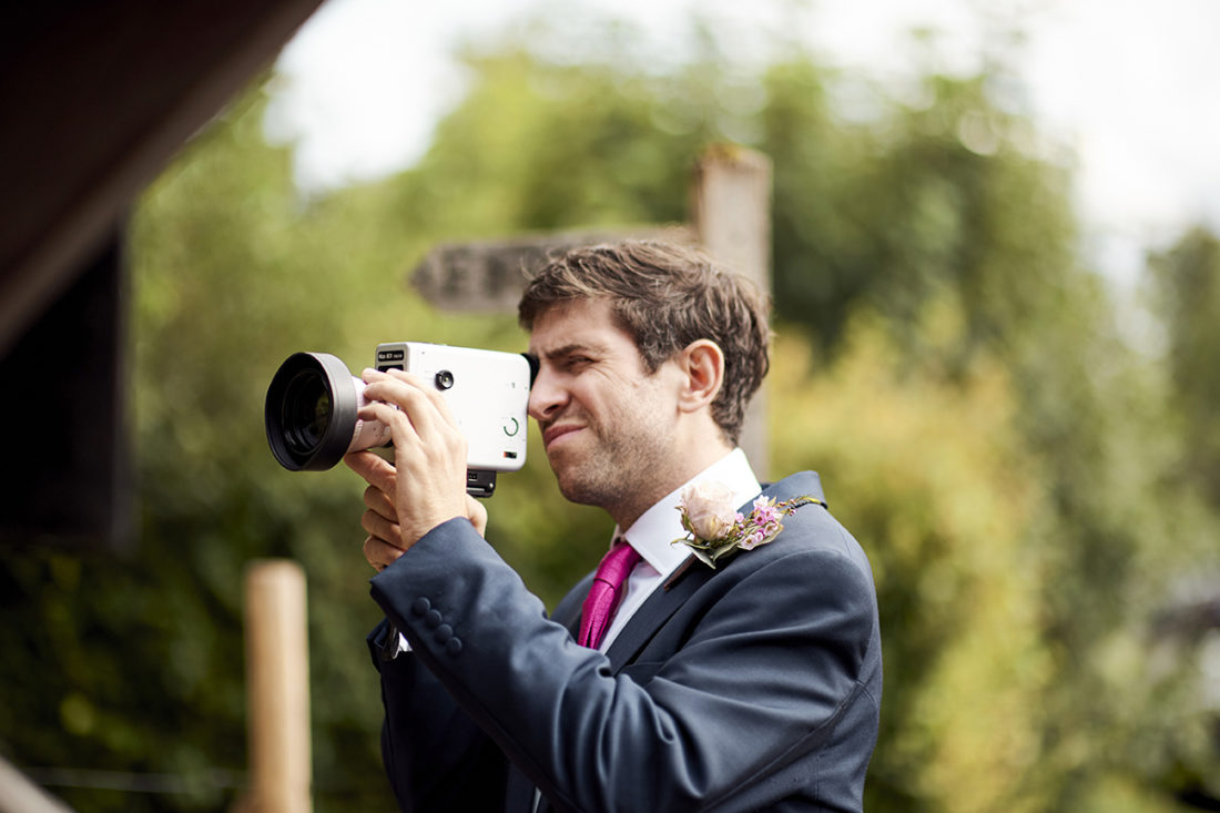 best man filming the wedding guests with old fashion camera