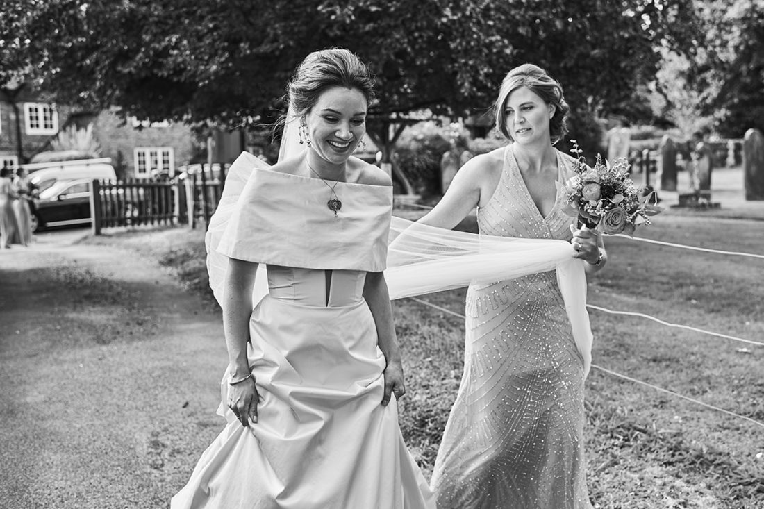 bride in romona keveza dress with bridesmaid holding veil kent luxury wedding
